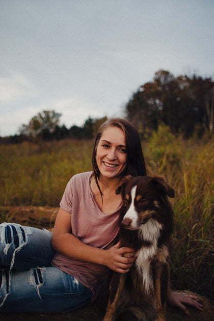 Eine Frau, die mit ihrem Hund bequem auf einer Wiese sitzt.